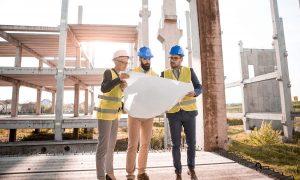 Équipe qui regarde un plan de construction en bâtiment